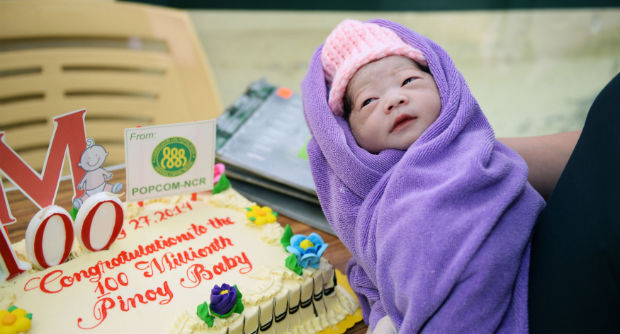 """A nurse holds the symbolic """"100 millionth Filipino baby"""", the baby making the Philippines' population hit 100 million, during a ceremony shortly after its birth early on July 27, 2014 at a government maternity hospital in Manila. (Photo by AFP via Inquirer.net)"""